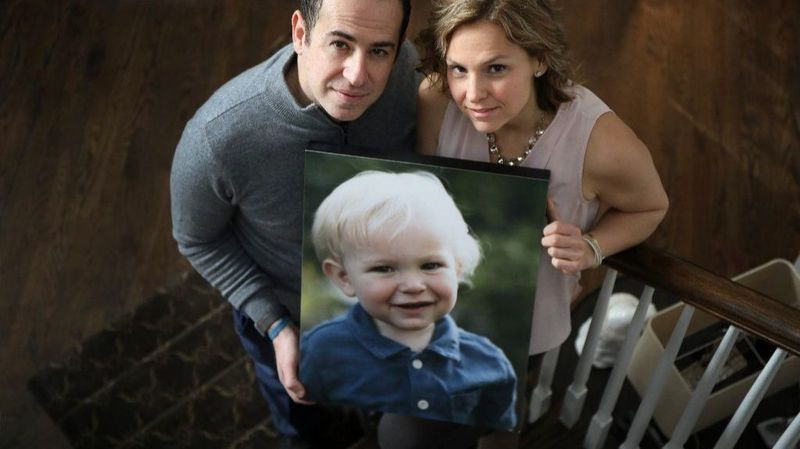 Greiving parents holding photo of dead son