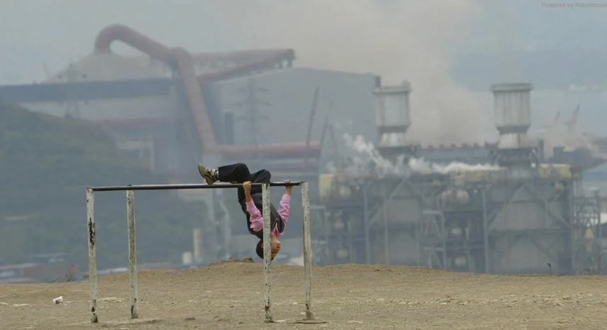 Child playing against backdrop of pollution